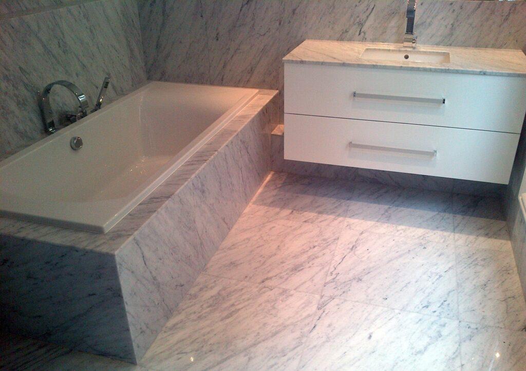 Salle de bain sur mesure, habillage de la baignoire et revêtement de sol et murs en marbre blanc de carrare. Paris 75008.